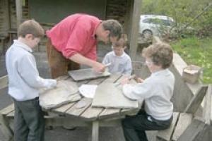 Gabriel Hummerstone helps children cut their chosen words into the slate.