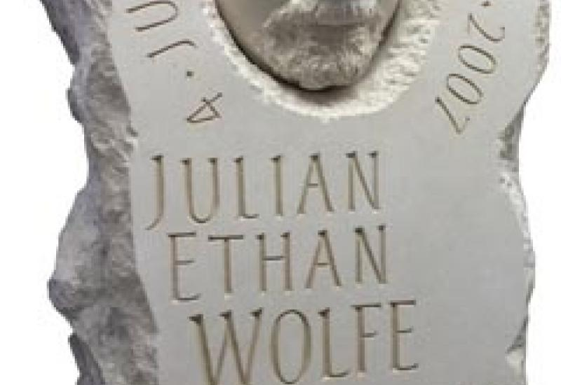 A death mask incorporated into this Portland limestone memorial by Joss Nankoo.