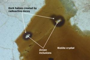 Orange-brown biotite mica, a common constituent of granite and many other stones, typically exhibits zircon inclusions with associated dark haloes.