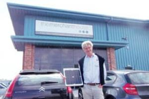 Charles Cogger, owner of worktop company The Merchant House, with one of the PV panels that are generating green electricity for his business.