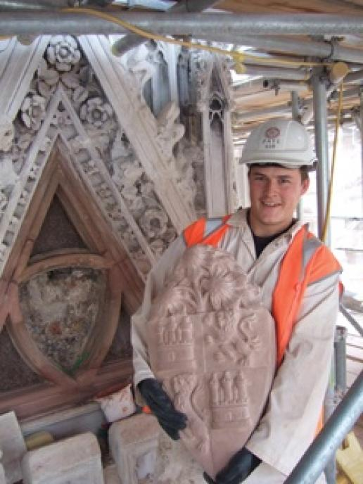 Rob Bessell holding a Red Mansfield shield on the back of which the masons have inscribed their initials.
